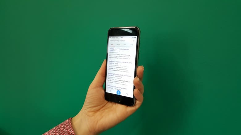A picture of a phone with a google search on the screen
