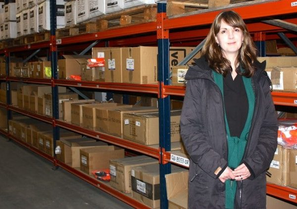 A woman standing in a warehouse with shelves around her