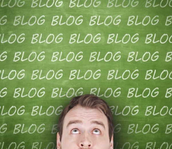 A man looking up at a wall with the word blog repeated on it
