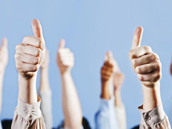 Several hands in the air with their thumbs up