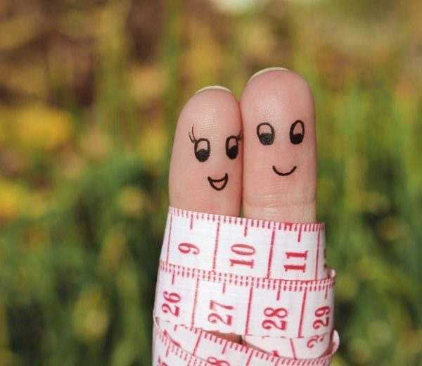 Two fingers with smiling faces tied together with a tape measure