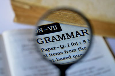 A magnifying glass hovering over a dictionary, highlighting the word grammar