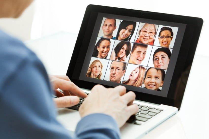 A person working on a laptop with 12 pictures of peoples faces being displayed