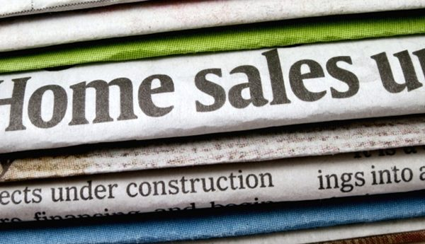 "A newspaper headline which reads ""Home sales up"""