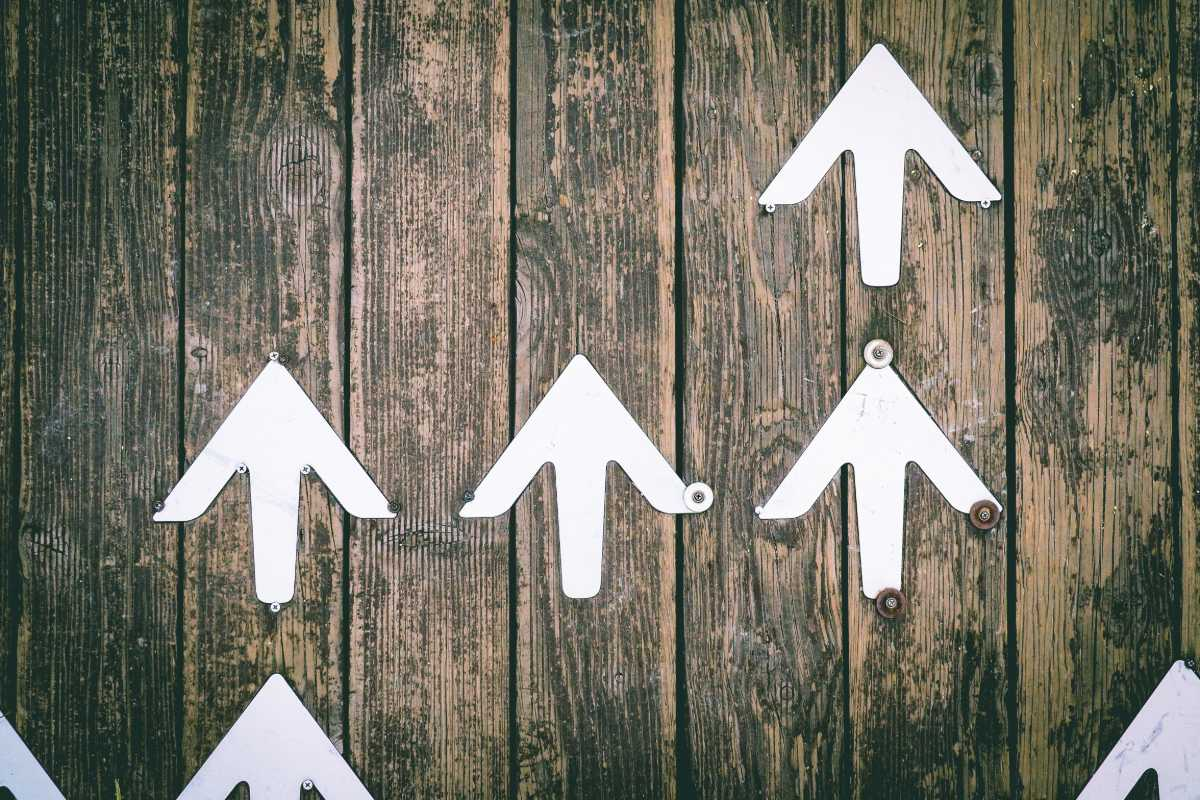 White Arrows on a wooden backdrop pointing upwards