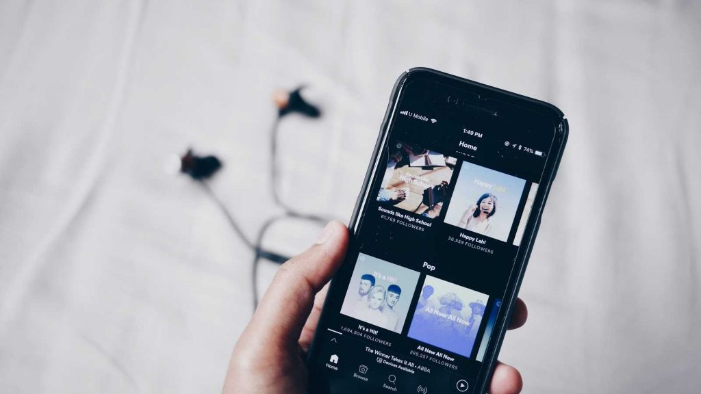 Spotify on an iPhone with headphones in the background