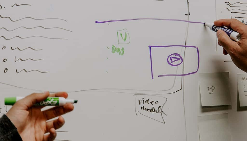 An image of two people planning content on a whiteboard